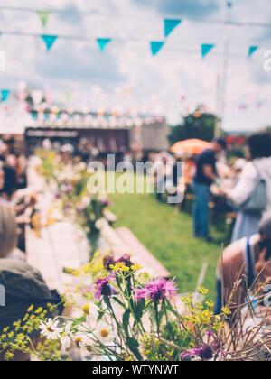 Bouquets de fleurs sauvages sur les tables en bois, pelouse verte, drapeaux colorés contre ciel clair Banque D'Images