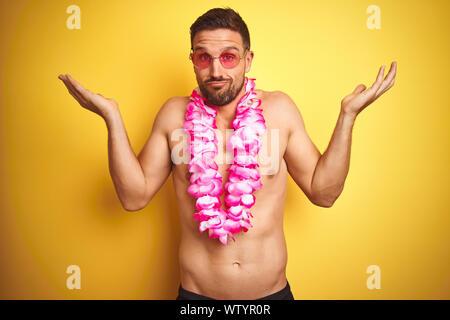 Beau jeune homme torse nu portant des lunettes de soleil et roses Hawaiian lei sur fond jaune clueless et expression confus avec les bras et les mains rais Banque D'Images