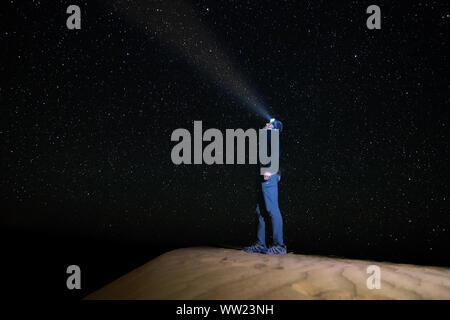 Un homme debout regardant le ciel étoilé avec une lampe de poche, sur une dune dans le désert de l'Erg Chebbi. L'astrophotographie Banque D'Images