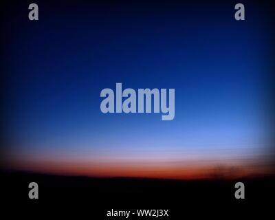 Silhouettes d'arbre sur un beau lever de fond de ciel, bleu foncé et rouge paysage flou Banque D'Images