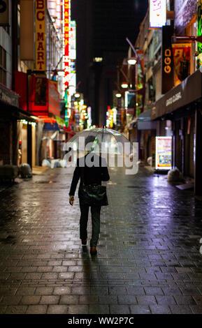 Homme marchant sous la pluie avec parapluie de nuit Banque D'Images
