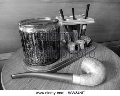 Image en noir et blanc de 3 vintage pipes et tabac container de stockage sur un support à 1 tuyau allongé sur la table Banque D'Images
