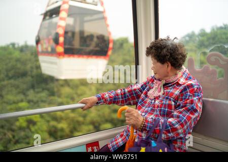 Taipei, Taiwan - 09. Avril 2019: grand-mère taïwanais à la fenêtre de sortie, profitant de la balade en gondole gondole Maokong, deuxième fenêtre extérieur Banque D'Images
