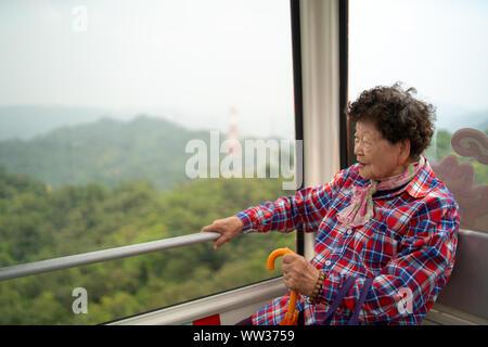 Taipei, Taiwan - 09. Avril 2019: grand-mère taïwanais à la fenêtre de sortie, profitant de la balade en gondole Maokong Banque D'Images