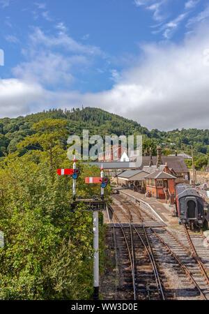 La gare de Llangollen en dessous d'une colline couverte d'arbres. Les wagons sont dans un garage et il y a un signal à l'avant-plan. Banque D'Images
