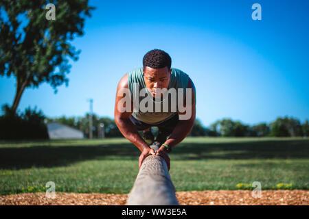 Un athlète solide sur les soldes en faisceau unique park performing pushups Banque D'Images