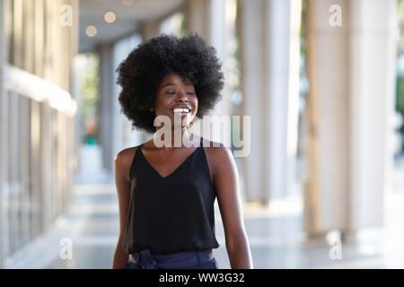 Souriante jeune femme noire marcher dans la ville profitant de la journée ensoleillée avec ses yeux fermés