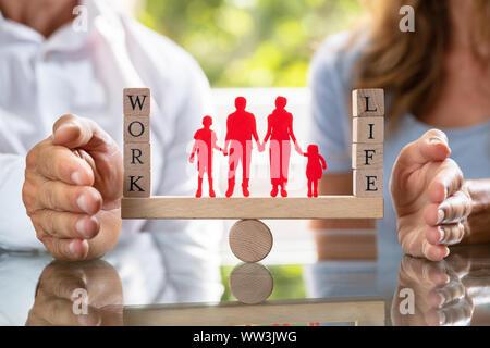 Couple de la protection du travail et la vie personnelle avec la famille des chiffres sur Seesaw Banque D'Images