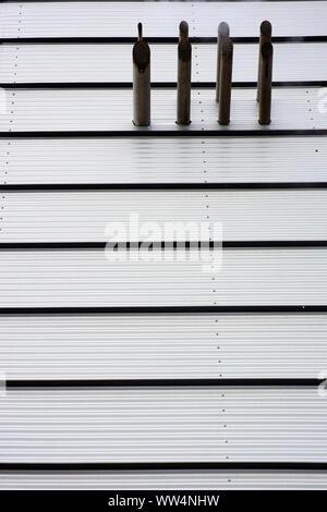 Photographie d'une façade de maison moderne à partir de la tôle ondulée avec des pipes alignées, Banque D'Images