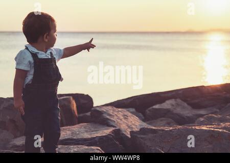 Tout-petit pointe vers le haut avec sa main tout en se posant en mer au coucher de soleil avec des couleurs chaudes