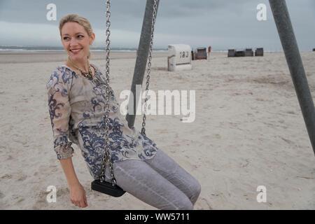 La moitié femme portrait sur la plage assis sur swing avec chaises de plage et mer en arrière-plan Banque D'Images