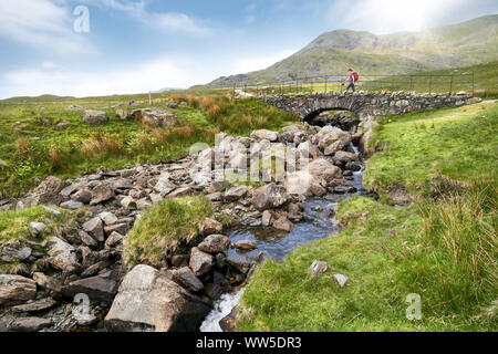 Passage d'un randonneur Torver Bridge près de Coniston sous le soleil d'été dans le Lake District. Banque D'Images