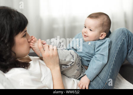 Bisous mère les pieds du bébé et joue avec lui dans ses mains. Heureux en famille week-end à la maison Banque D'Images