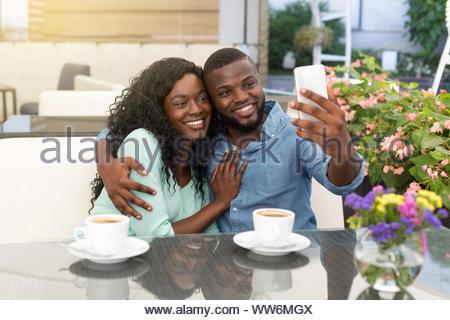 Couple d'amoureux romantique de boire du café et la prise de photo, ayant une date dans cafe Banque D'Images