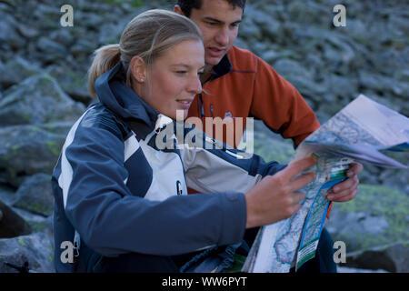 Jeune couple reading a map sur Am Hügel 7¶henweg, Hôtel Alpes de Zillertal, Tyrol, Autriche Banque D'Images