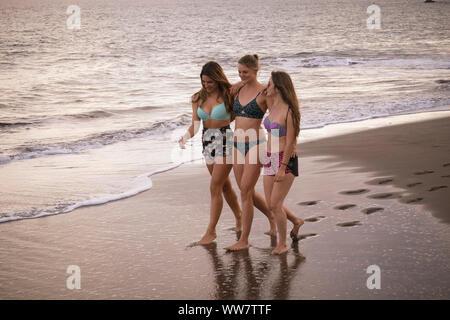 Portrait de trois jeunes femmes gaies marcher ensemble embrassé sur le rivage à la plage. L'été activités de plein air vie pour de belles jeunes filles en vacances. smiling jours et le bonheur