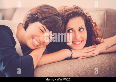 Beau temps et bonheur avec rire et sourire pour deux amis caucasiens fixer ensemble sur le canapé à la maison. L'amitié pour l'intérieur concept photo avec fenêtre lumière naturelle Banque D'Images