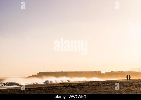Couple de personnes traveler les touristes à marcher ensemble à la plage au cours d'une vague tempête. coucher du soleil lumière dorée avec grande vague en arrière-plan Banque D'Images