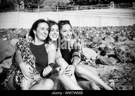 Groupe de belle femme jeune et souriant parlant autour d'une plage de galets de Tenerife. équipe filles de s'amuser ensemble Banque D'Images
