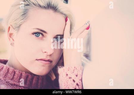 Portrait de flou artistique avec l'accent sur les yeux clairs d'une belle jeune fille de race blanche modèle russina s'asseoir et à la recherche pour vous sur appareil photo. petit sourire détendu pour concept de vie Banque D'Images