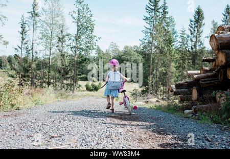 Jeune fille qui marche avec son vélo le long d'un chemin de campagne en été
