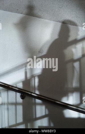 Résumé fond d'ombres homme en montant les escaliers et l'éclairage sur un mur blanc. Banque D'Images