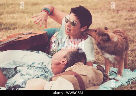 Scène romantique vintage avec jeune belle femme et l'homme s'étendit sur l'herbe profitant de la journée, peu de jeunes animaux de l'embrasser, Shetland et pacifique hippy love concept et musique avec guitare Banque D'Images