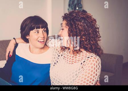 Beau temps et bonheur avec rire et sourire pour deux amis caucasiens fixer ensemble sur le canapé à la maison, concept d'amitié pour l'intérieur photo avec fenêtre lumière naturelle Banque D'Images
