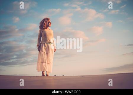 Belle jeune femme d'âge moyen 40 ans profitez du soleil sur son visage et son corps, et de l'été vacances activité de loisirs concept, Ciel et nuages de fond, les personnes de race blanche à l'extérieur Banque D'Images