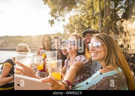 Groupe de jeunes beaux caucasian woman prenant en selfies locations activité de loisirs piscine près de la plage et l'océan, l'heure du coucher du soleil avec rétroéclairage et beaucoup de sourires et de bonheur ensemble dans l'amitié pour toujours Banque D'Images