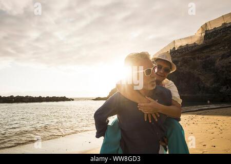 Happy senior couple dans l'amour, l'homme sur son dos la belle femme et deux sourires, vie affective et ensemble pour toujours dans le concept des vacances avec le coucher du soleil et des vagues de l'océan Banque D'Images