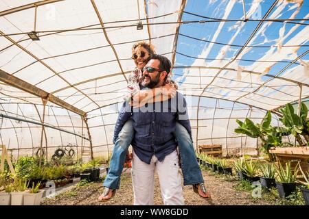 Jolie femme avec de longs cheveux bouclés est à cheval sur l'arrière de bel homme dans le domaine de l'agriculture place shop, une personnes de race blanche de s'amuser ensemble, mariés et de l'amour sous un concept ensoleillé en place biologique Banque D'Images