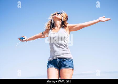 Attrayant beau joyeux caucasian middle age woman smiling at the beach in tropical place tandis que écouter de la musique avec le téléphone intelligent, les personnes bénéficiant de la liberté de travail et de vacances Maison de vacances Banque D'Images