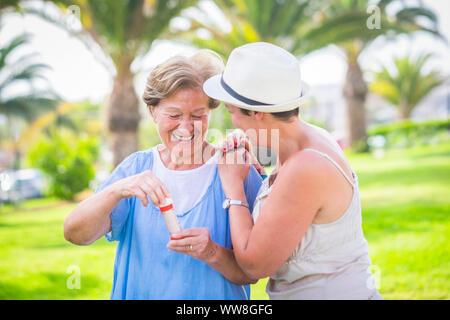 Deux âges différents comme mère et fille jouer ensemble dans l'activité de loisirs de plein air avec des bulles de savon, de profiter de la journée dans le parc avec des plantes vertes, des couleurs vives fond tropical Banque D'Images