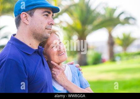 Deux âges différents comme mère et fils - rester ensemble dans l'activité de loisirs de plein air avec amour et d'émotions, profiter de la journée dans le parc avec des plantes vertes, des couleurs vives fond tropical Banque D'Images