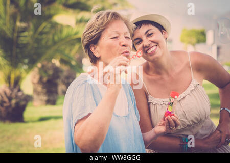 Deux âges différents comme mère et fille jouer ensemble dans l'activité de loisirs de plein air avec des bulles de savon, de profiter de la journée dans le parc avec des plantes vertes contexte tropical, filtre vintage Banque D'Images