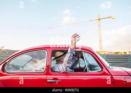 Portrait d'âge mûr et de voyage en voiture sur une voiture vintage rouge. Locations et wonderlust concpet pour gens heureux déménagement partout dans le monde. accueil bâtiment en arrière-plan Banque D'Images