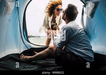 Couple d'hommes et de femmes de race blanche de 40 ans dans l'amour à la plage dans camping lieu tropical, vivant près de l'océan et profiter de vacances en tente. kiss et phare en arrière-plan Banque D'Images