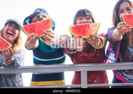 Quatre belles jeunes femmes happy woman eating watermelon pour célébrer l'été et chaude journée avec soleil près de l'océan. belles couleurs pour groupe d'amis les gens de manger des fruits et de la pastèque smiling folie Banque D'Images