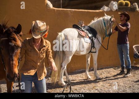 Couple dans la campagne préparer les chevaux pour aller en voyage de plein air et découvrir de nouvelles plces en excursion. ntaural de vie de plein air pour le bonheur et la zoothérapie Banque D'Images
