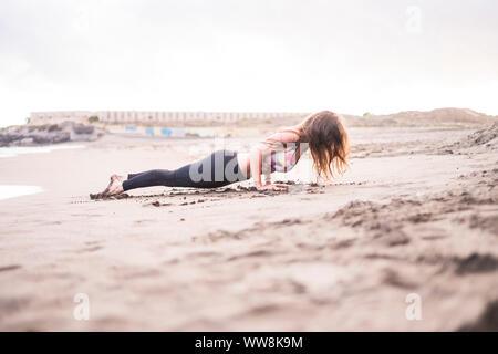 Planche parfaite pour de belles young caucasian dame à la plage sur la côte. journée ensoleillée en loisirs en plein air, activités sportives en force et d'exercice équilibré pour faire un corps parfait Banque D'Images