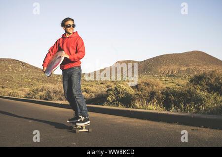 Jeune beau mâle adolescent aller à la plage avec la planche à roulettes transportant un tableau de surf pour l'activité de l'eau dans l'été. piscine Loisirs pour nice people smiling Banque D'Images