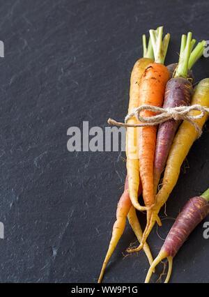 Groupe de produits frais bio carottes arc-en-ciel sur un fond sombre Banque D'Images