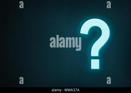 Point d'interrogation au néon s'allume sur un fond sombre, le concept de trouver la réponse à une question ou trouver une solution. Banque D'Images