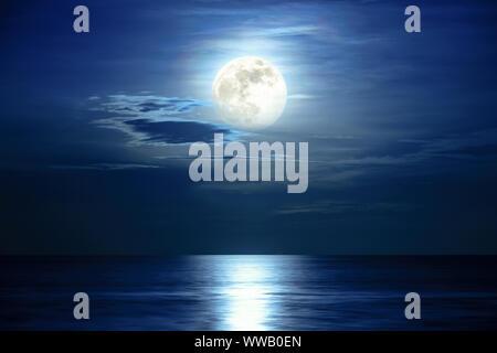 Super pleine Lune et nuage dans le ciel bleu au-dessus de l'horizon de l'océan à minuit, moonlight reflètent la surface de l'eau et des vagues, belle nature paysag Banque D'Images
