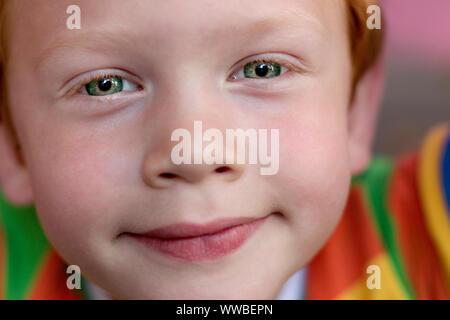 Gros plan du beau garçon des yeux. Portrait enfant aux yeux verts à directement à l'appareil photo. Drôle de petit enfant avec des cheveux bouclés le gingembre. Vision
