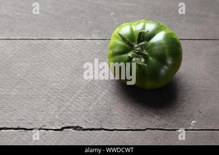Ils ne sont pas mûrs, tomates du patrimoine vert sur une table en bois rustique Banque D'Images