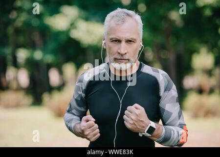 Confiant dans la musique à l'écoute de sportif à maturité en faisant du jogging dans le parc d'écouteurs Banque D'Images
