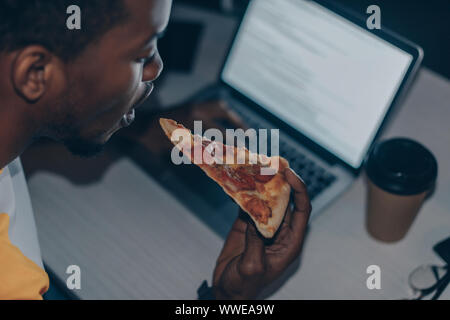 Young african american programmer eating pizza tout en travaillant de nuit in office