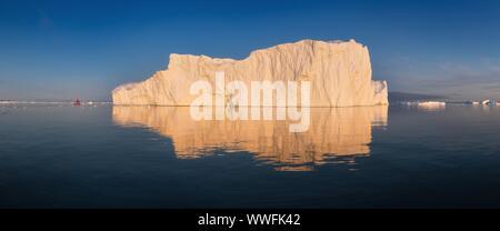 Croisière voilier rouge parmi des icebergs dans la baie de Disko glacier durant la saison de soleil de minuit de l'été polaire. Ilulissat, Groenland. L'Unesco